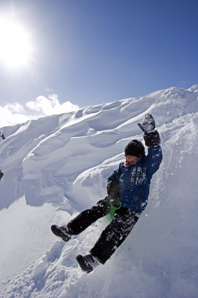 Stock Photo: 4272-24422 Norway, Tromso, Lyngen Alps.   Young boy has extreme fun tobogganing in bright winter son. (MR)
