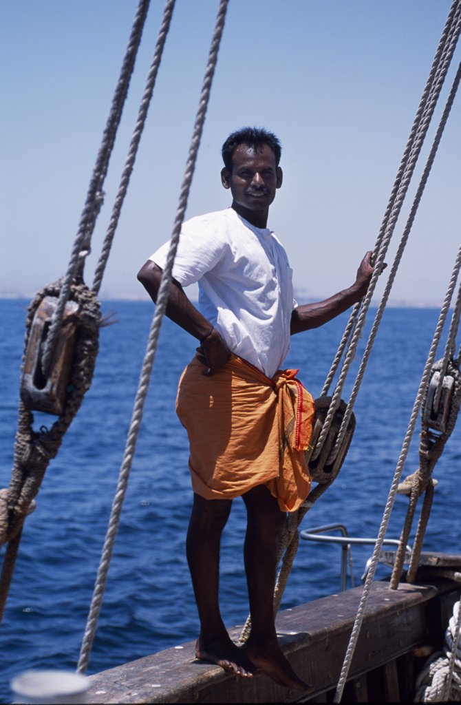 Stock Photo: 4272-24965 One of the crew members of S/Y Sanjeeda standing on the rail of the boat.  Sanjeeda is a traditional kotiya dhow of the type that traded  throughout the Indian Ocean