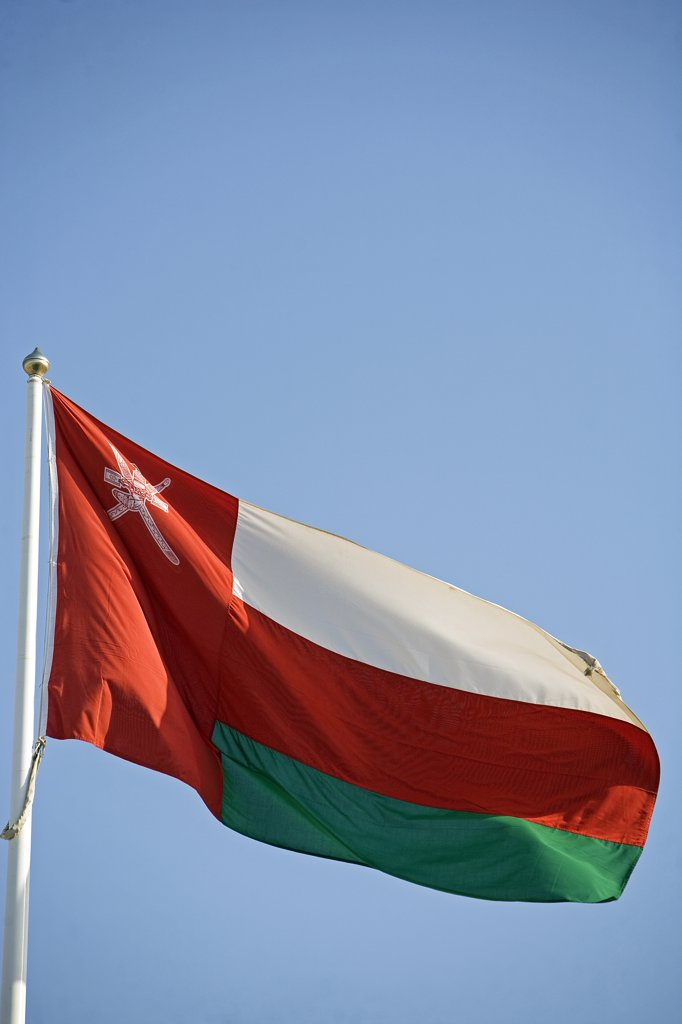 Stock Photo: 4272-25072 Oman. The National Flag - this flag contains the country's national coat of arms which is a khanjar dagger in a sheath that is superimposed upon two crossed swords. This is the traditional symbol of Oman. It is found on numerous flags as well as the currency of Oman.