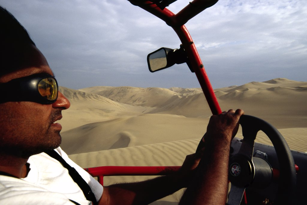 Stock Photo: 4272-25573 Riding in the front seat of a dune buggy, as the driver navigates the sand dunes near Ica, in southern Peru
