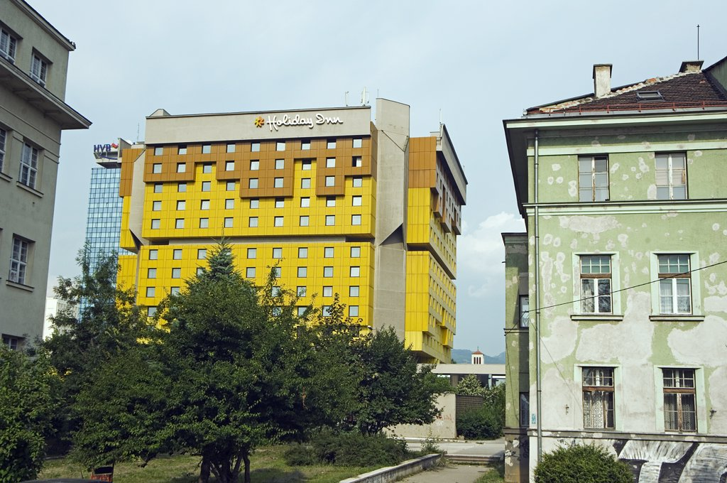 Stock Photo: 4272-2563 Sarajevo Holiday Inn on 'Sniper Alley' newly repainted next to heavily war damaged houses