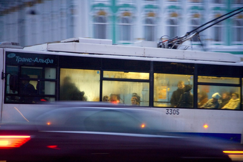 Russia, St. Petersburg; A trolley bus passing in front of the State Hermitage Museum in the evening : Stock Photo