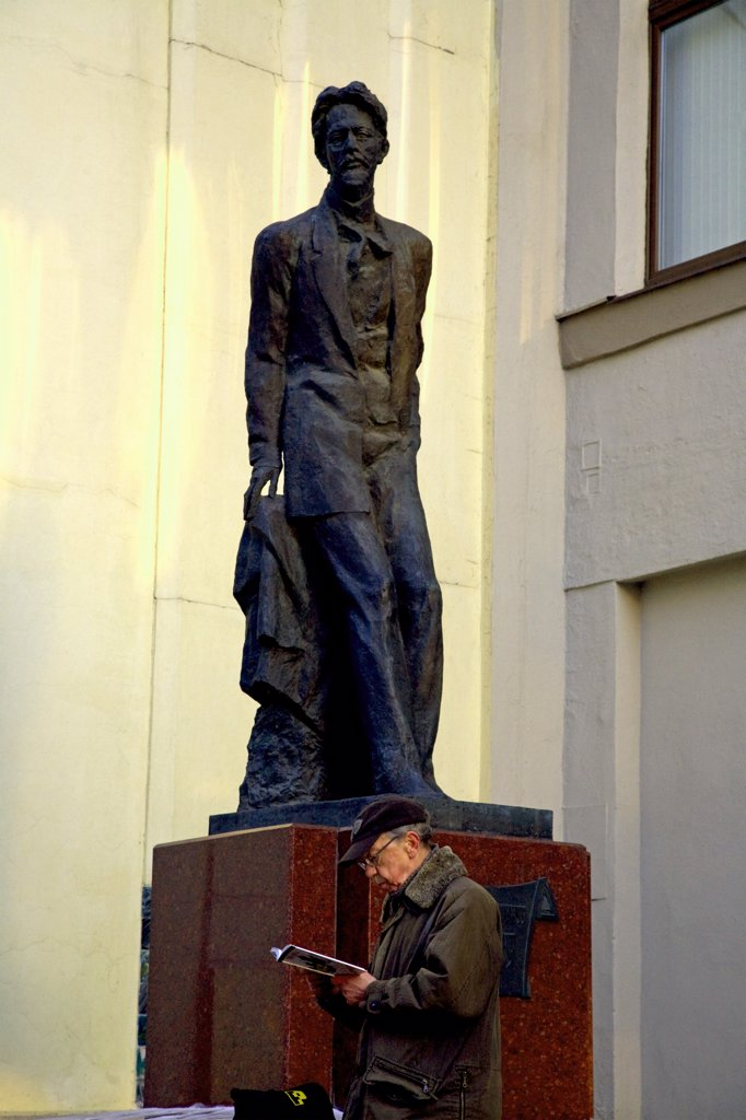 Stock Photo: 4272-27526 Moscow, Russia; Tourist in front of a monument to Anton Chekhov in the historical centre, an icon amongst Russian writers and dramatists