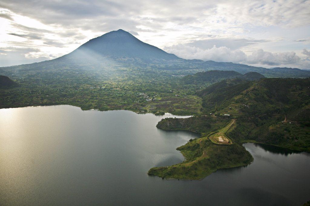 Rwanda. Lake Burero reaches out underneath the volcanoes. The volcanic lakes provide protected habitat for numerous species of birds. : Stock Photo