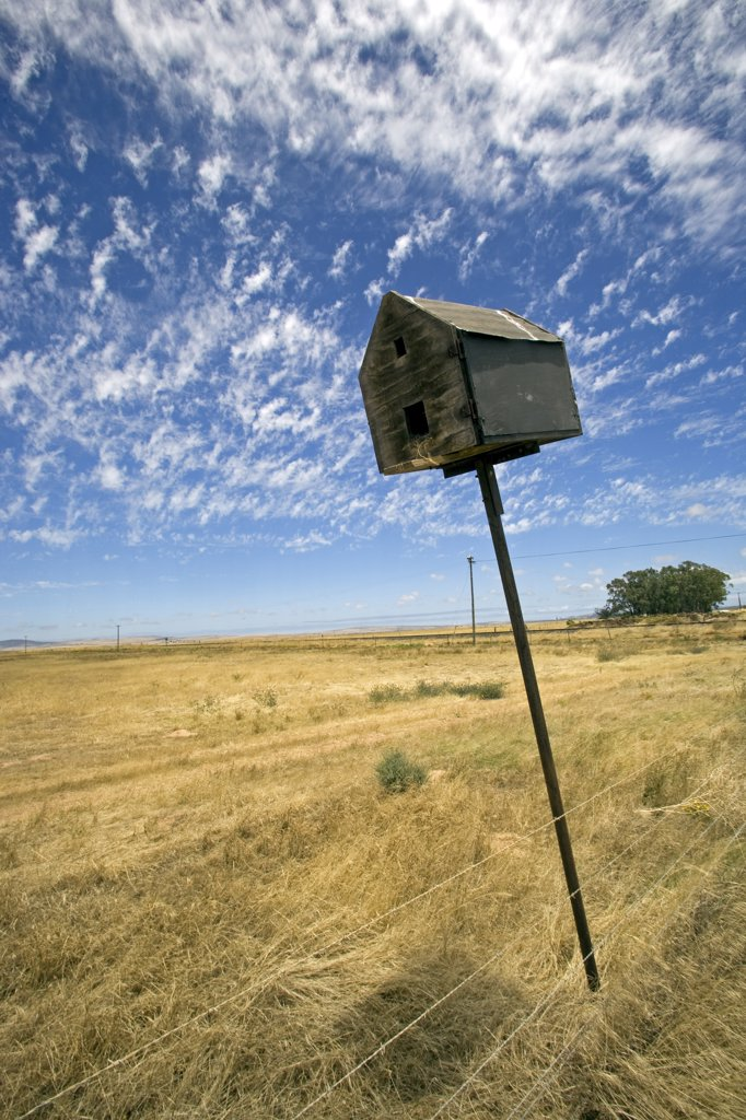 Stock Photo: 4272-28064 South Africa, Western Cape, Swartland, Darling.  An abandoned bird box leaning lazily to one side on farmland near the small town of Darling.