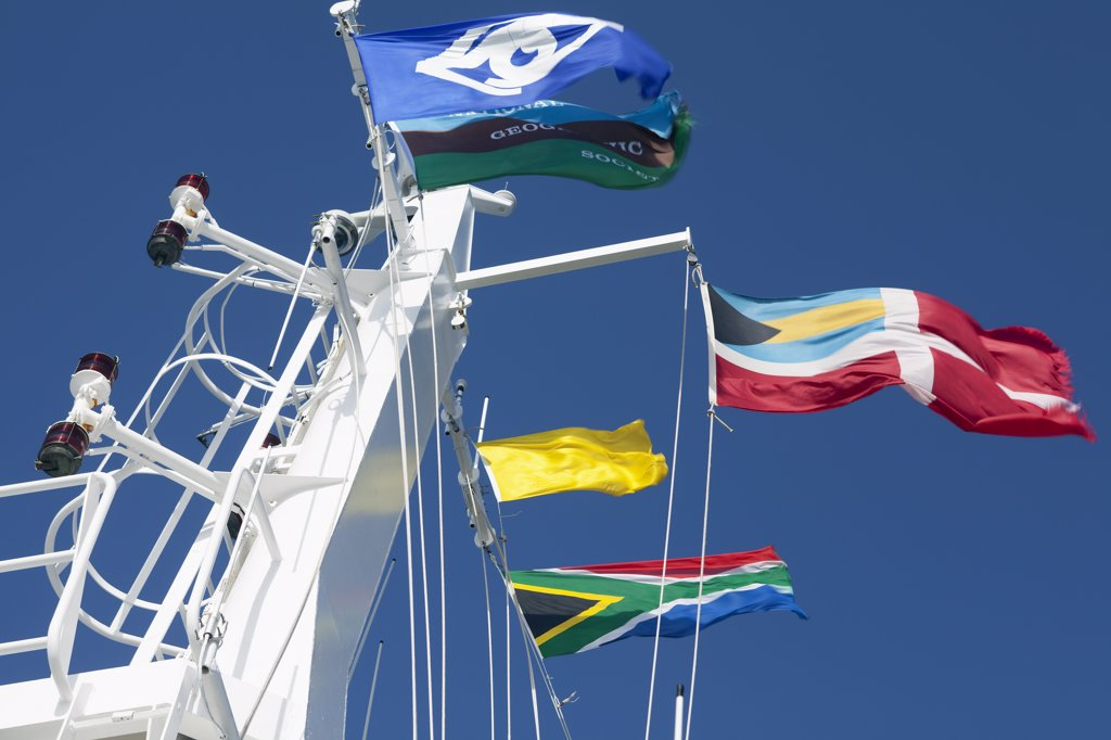 South Africa, Cape Town.   On the forecastle mast of the National Geographic Explorer owned by Linblad Expeditions a flurry of curtesy flags whip back on forth in strong winds on entry to Cape Town Port. : Stock Photo
