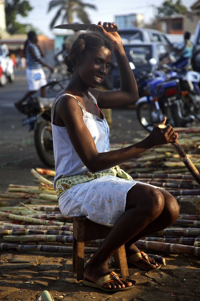 Stock Photo: 4272-28753 A Sao Tomense woman strips the outer skin of a piece of sugar cane in the market of Sao Tome. It is common to chew on the sugar cane, especially for children. Sugarcane was once a major export in the first half 17th century. Sao Tome were at this time the largest exporters in the world.