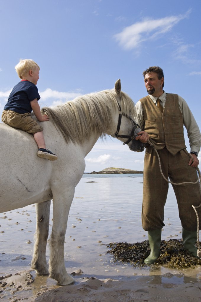Gordon Muir, stalker and ghillie at Glen Batrick Lodge, leads young guest from the lodge along the shore of Loch Tarbert on a Highland pony : Stock Photo