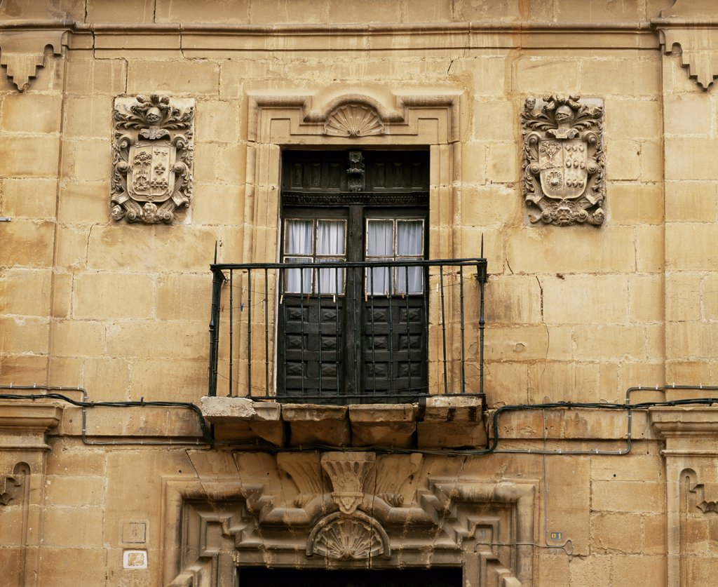 Details of carved armorial shields and a window and wrought iron balcony on a mansion in Haro : Stock Photo