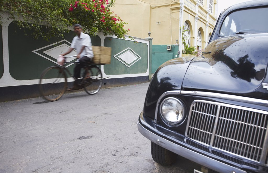 Man cycling past parked Morris Minor on Pedlar Street in Galle Fort, Galle, Sri Lanka : Stock Photo