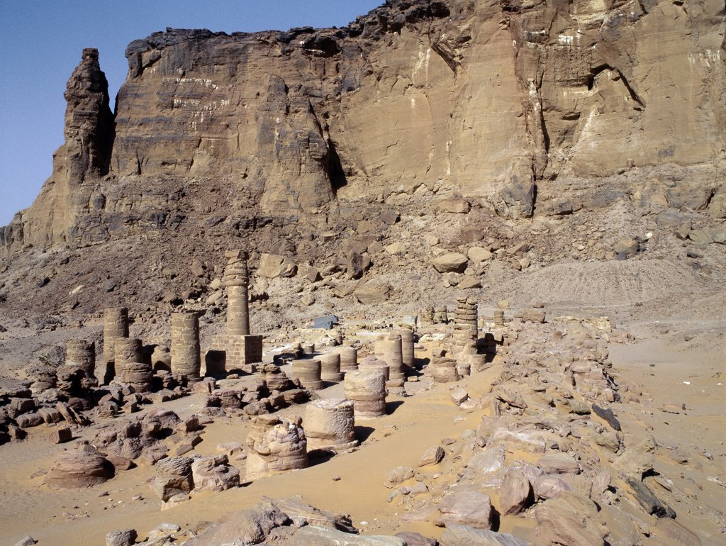 The ruins of an Egyptian temple dedicated to God Amon at the foot of Jebel Barkal Mountain.  The Egyptian New Kingdom (1521-1075 BC) regarded Jebel Barkal as a holy mountain, the seat of God Amon, and built several temples there. The Black Pharaoh Taharqa subsequently extended this temple.  Amon was revered in both Egypt and the Kingdom of Cush as king of the Gods. : Stock Photo