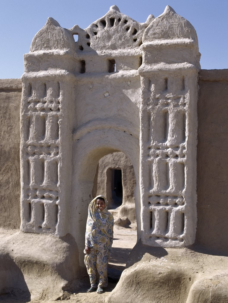 Stock Photo: 4272-31292 A Nubian girl stand in an archway at the village of Qubbat Selim.  Traditional Nubian architecture. Traditional Nubian architecture and plasterwork of a fine archway to a house and its courtyard at Qubbat Selim.