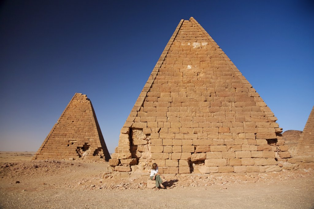 Stock Photo: 4272-31342 Sudan, Karima. A tourist sits at the base of an ancient pyramid at Karima.