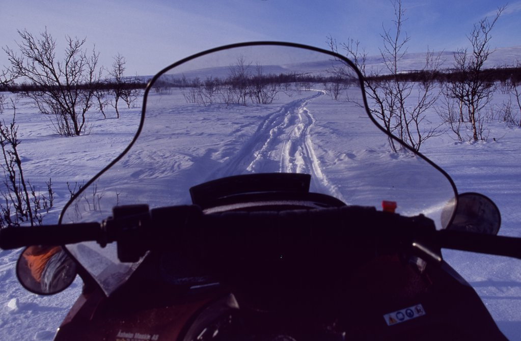 Stock Photo: 4272-31392 View over the front of a snowmobile on a trail through snow