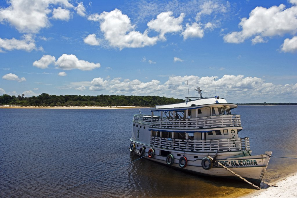 Stock Photo: 4272-3151 Brazil, Amazon, Rio Tapajos. A tributary of the Rio Tapajos which is itself a tributary of the Amazon has the Saude Alegria river boat secured its banks during the low waters of the dry season.