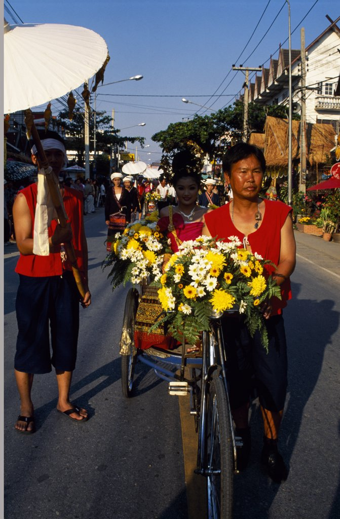 Man pushing bicycle filled with flowers at Parasol Festival, Chang Mai : Stock Photo