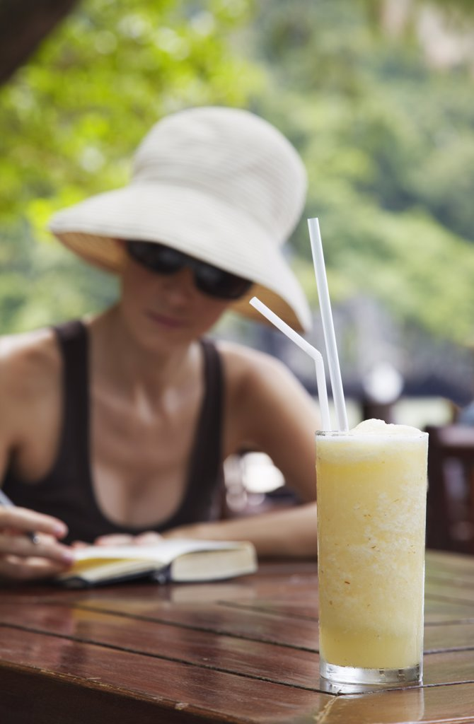 Stock Photo: 4272-32283 Woman at beachside restaurant with pineapple drink, Railay, Krabi Province, Thailand (MR)