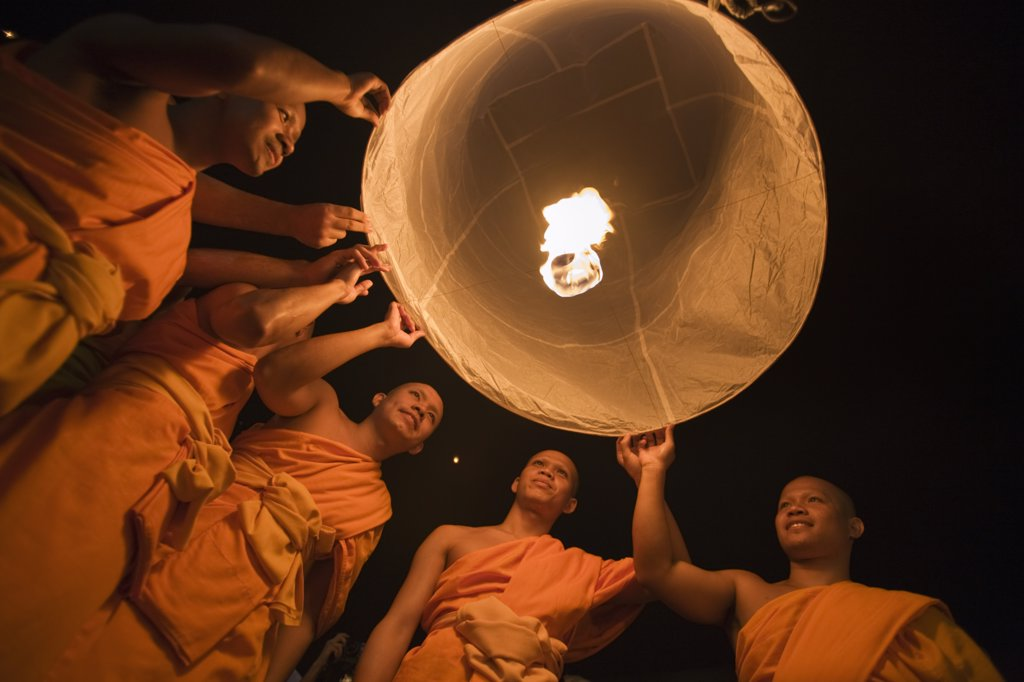 Stock Photo: 4272-32376 Thailand, Chiang Mai, San Sai.  Monks launch a khom loi (sky lantern) during the Yi Peng festival.  The ceremony is a Lanna (northern Thailand) tradition and coincides with Loi Krathong festivities.  The khom loi are released in the belief that grief and misfortune will float await them, bringing good luck.