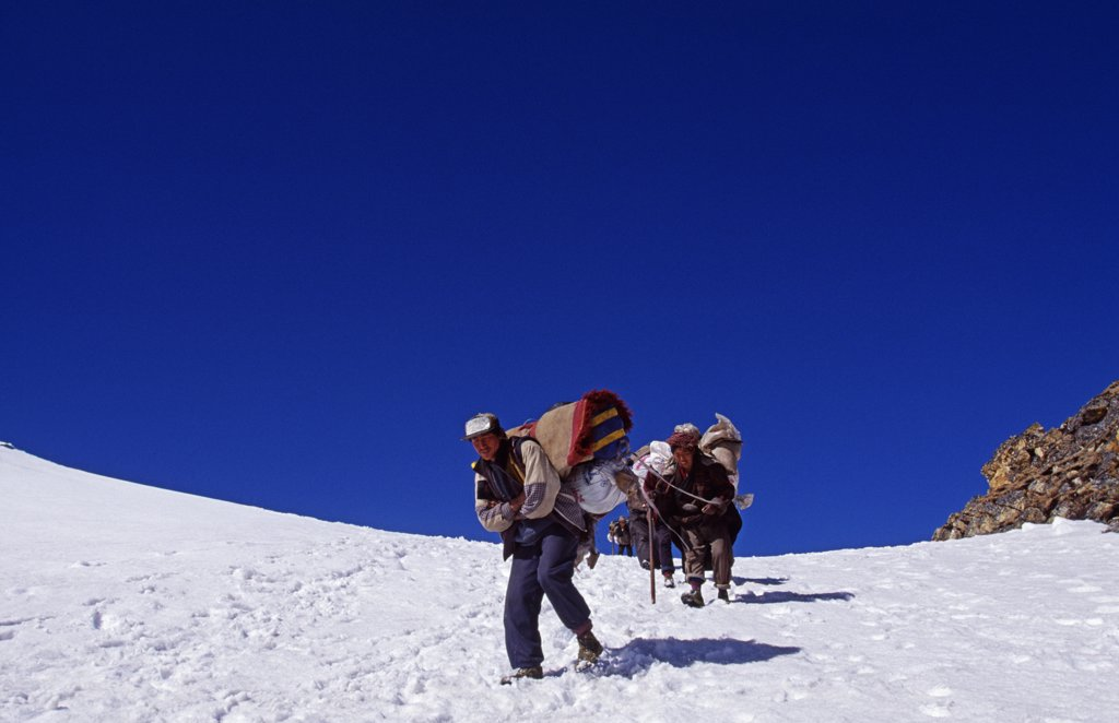 Tibet, Chomolungma, Kangshung Valley. Porters crossing the Sho La Pass into the Kangshung Valley on the way to the East side of Mount Everest. The Kangshung Valley was used by mountaineering expeditions seeking to climb Mount Everest in 1920's because Nepal was closed to foreigners. : Stock Photo