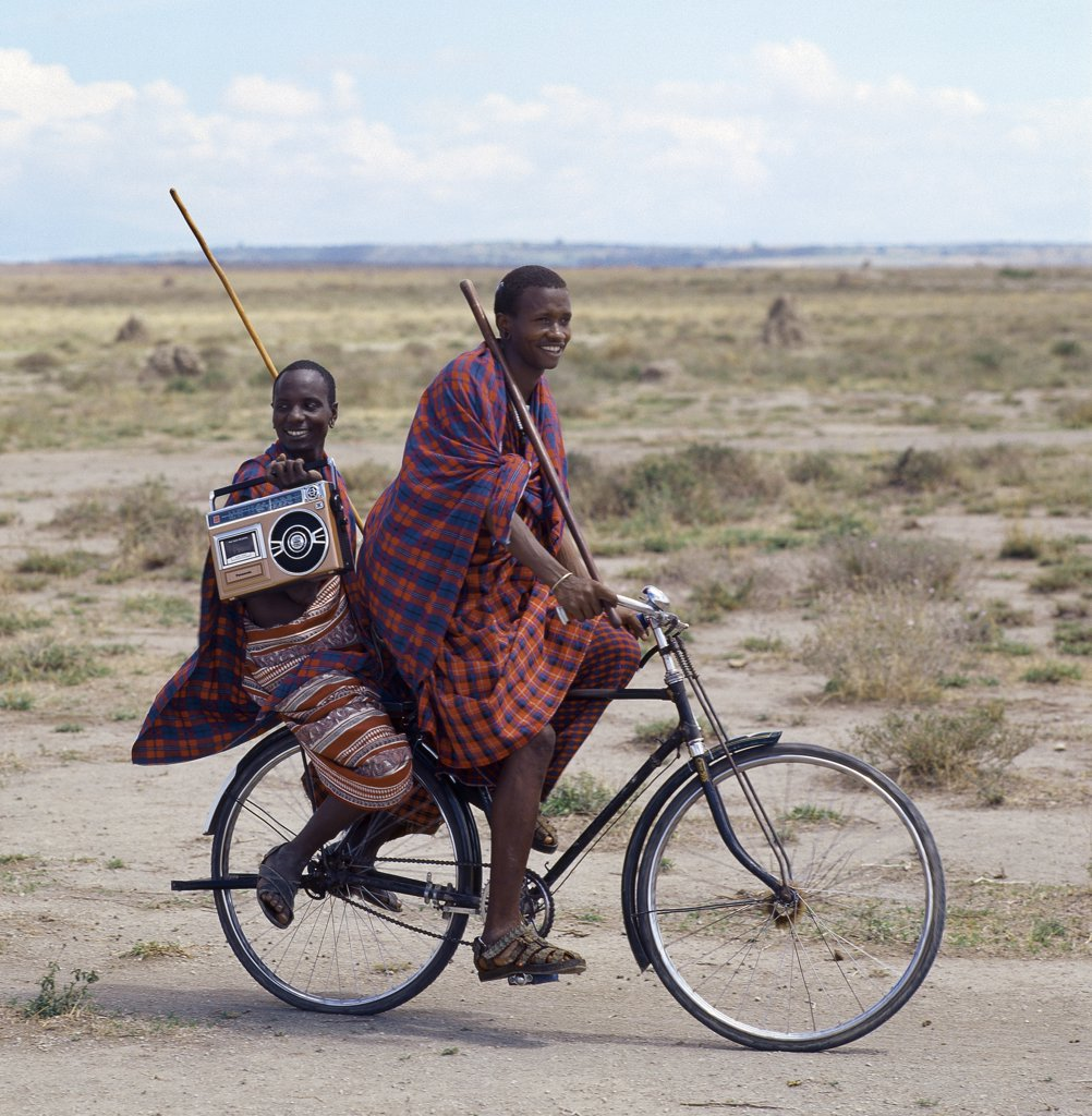 Stock Photo: 4272-32834 Old and new.  Dressed traditionally and carrying familiar wooden staff, two young men give hints that the lifestyle of younger Maasai generations is changing gradually in Tanzania.