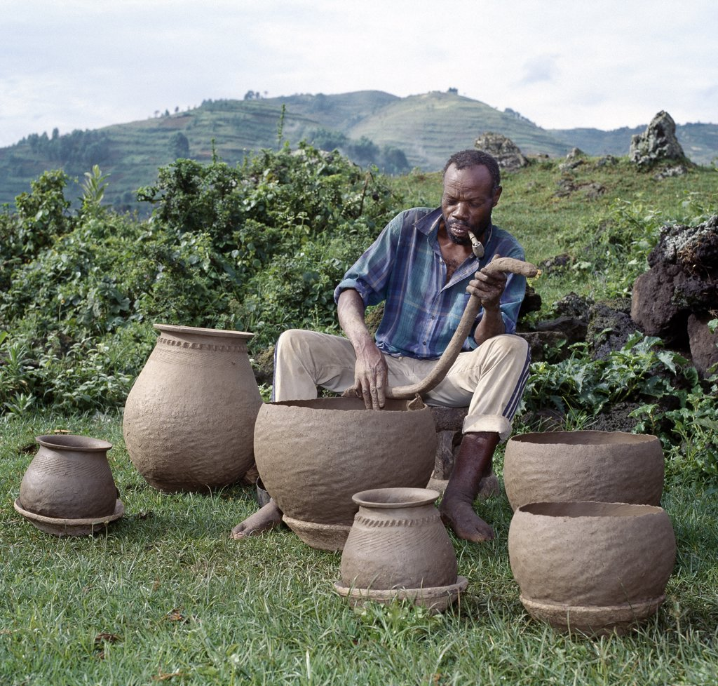 A potter fashions cooking pots by the coil method, shaping them by eye alone. Surprisingly, craft skills such as pottery and basket-making are the sole preserve of men in Southwest Uganda. : Stock Photo