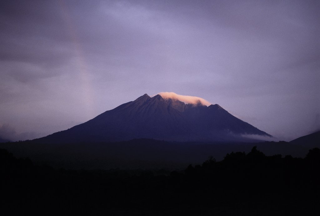 Mount Sabinyo (11,923 feet) is one of three volcanoes of the Virunga chain bordering Uganda. Its name in the local language means father with huge teeth because a row of five sharp rock pinnacles give the appearance of protruding from a long, curved jawbone (its summit ridge) : Stock Photo