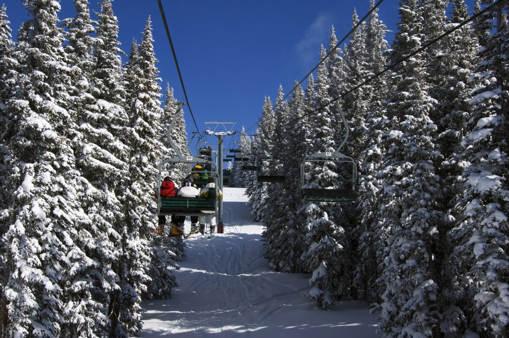 Stock Photo: 4272-34446 USA, Colorado, Vail Ski Resort. Skiers being carried on a chair lift in Vail back bowls