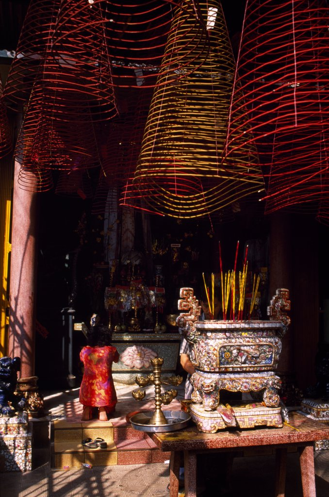 Stock Photo: 4272-34938 Woman praying at one of the shrines at Phoc An Hoi Quan Pagoda overlooked by coils of incense hanging from the roof interior .The Pagoda is surrounded by traditional turn-of-the-century Chinese merchant houses and dedicated to the Emperor Quan Cong.