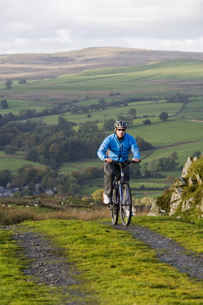 Stock Photo: 4272-35565 Gilar Farm, Snowdonia, North Wales. Man mountain biking on a farm track.  (MR)