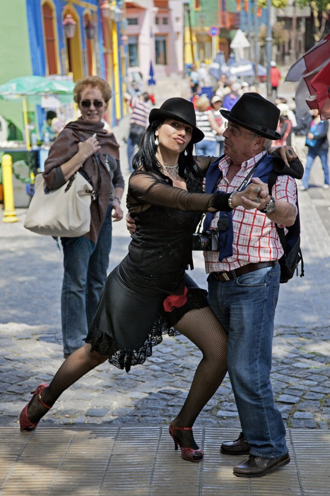 A light-hearted moment with a tango dancer and a tourist in a street at La Boca. : Stock Photo