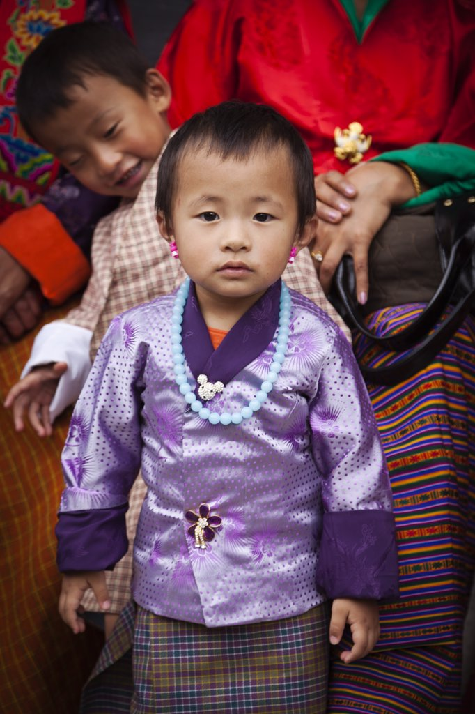 Stock Photo: 4272-36473 A smartly dressed child watching the masked dancing at Trashi Chhoe Dzong, a monastery now also housing the secretariat, the throne room and offices of the King.