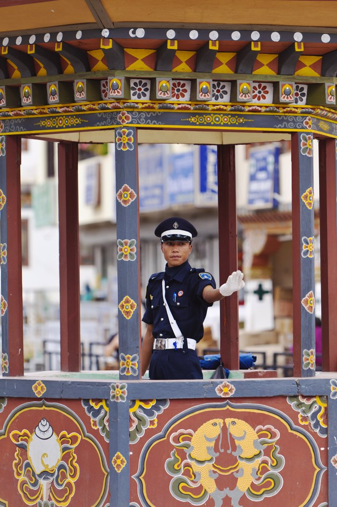 A traffic policeman directs traffic from his beautifully painted traffic island at a busy crossroads in Thimphu, the capital city of Bhutan. : Stock Photo