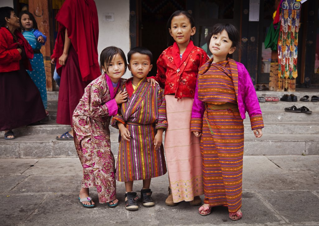 Stock Photo: 4272-36487 Children in traditional Bhutanese dress at the National Memorial Chorten, which was built in the Tibetan style in 1974 to honour the third king of Bhutan.