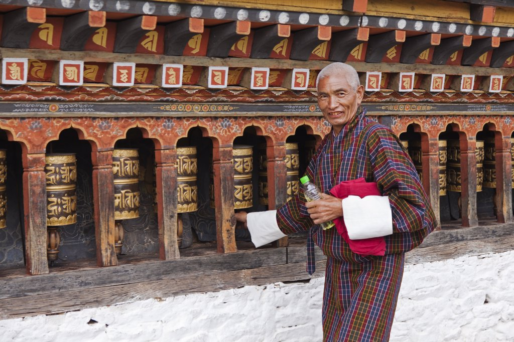 Turning the beautiful black and gold prayer wheels at Changangkha Lhakhang, where parents come to obtain auspicious names for their newborns. : Stock Photo
