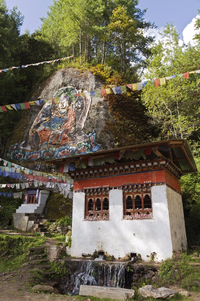 Stock Photo: 4272-36493 Rock painting of Guru Rinpoche en route to Tango Monastery. On the window ledges of the building sit small sculpture stupa images (tsha tsha) made of clay containing ashes of the cremated dead