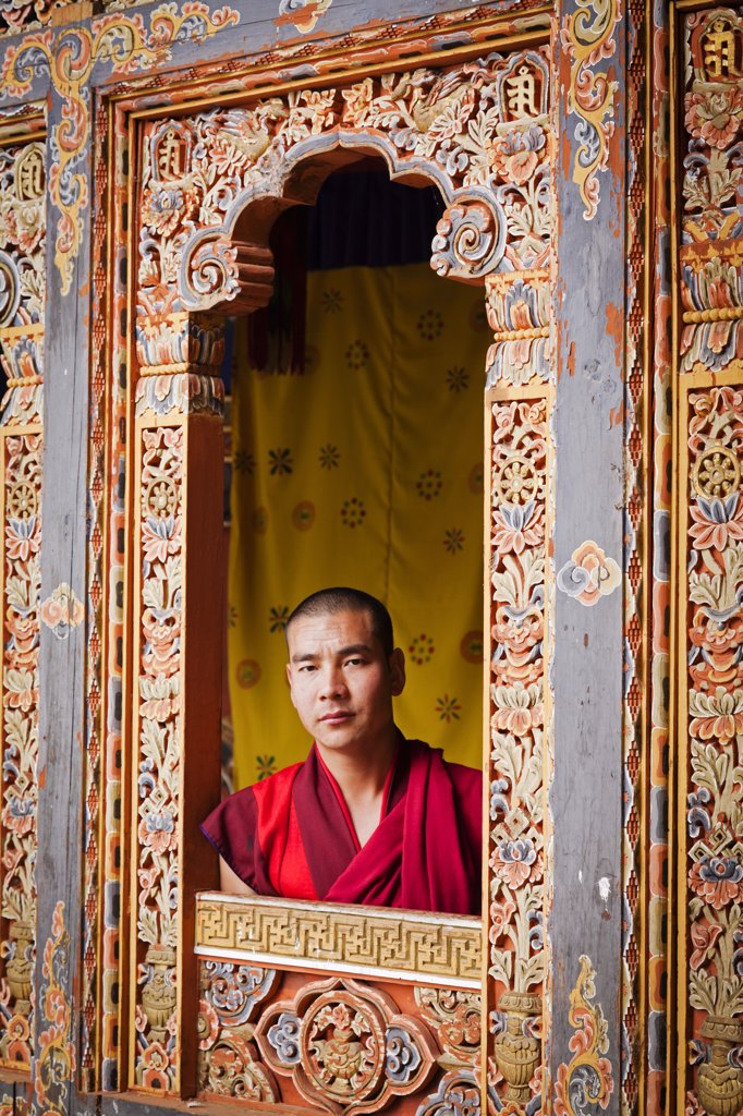 Young monk looking through one of the beautiful carved window frames at Tango Monastery. : Stock Photo