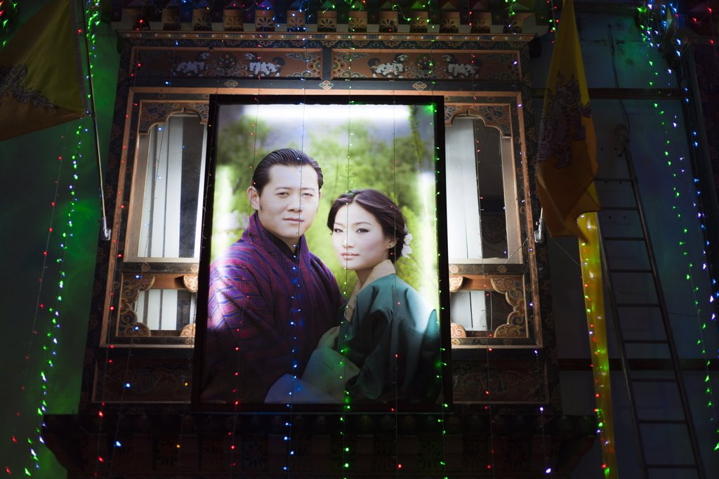 Stock Photo: 4272-36632 A large poster lit up on the side of a building in Thimphu showing the newly married King of Bhutan, and his Queen Consort, Jetsun Pema.