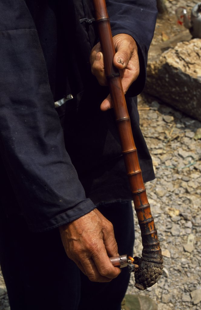 Stock Photo: 4272-3686 A villager lights his pipe