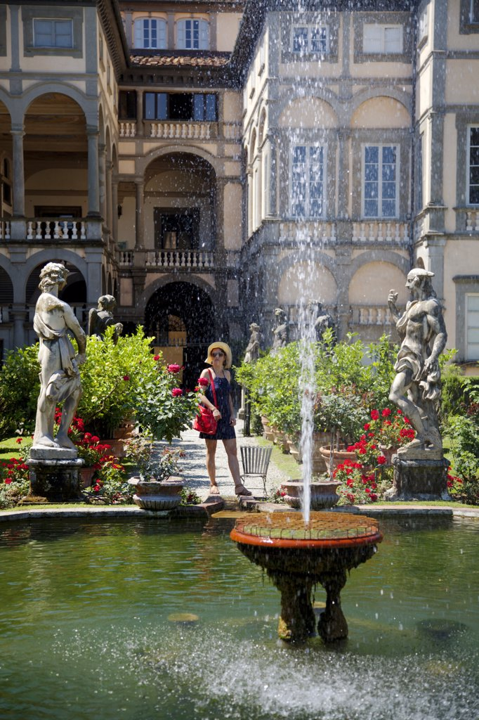 Stock Photo: 4272-37277 Italy, Tuscany, Lucca; A tourist enjoying the scenery of the gardens at Villa Pfanner. MR