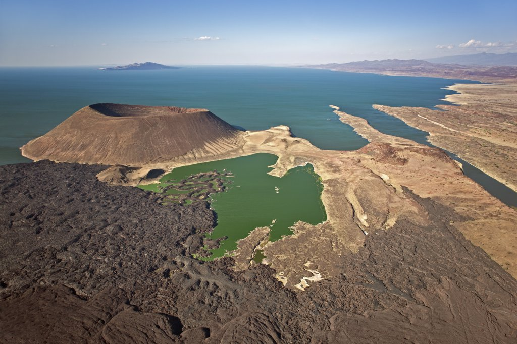 The perfectly shaped volcanic cone called Nabuyatom juts into the jade waters of Lake Turkana at the inhospitable southern end of the lake, known as Von Hohnel Bay. : Stock Photo