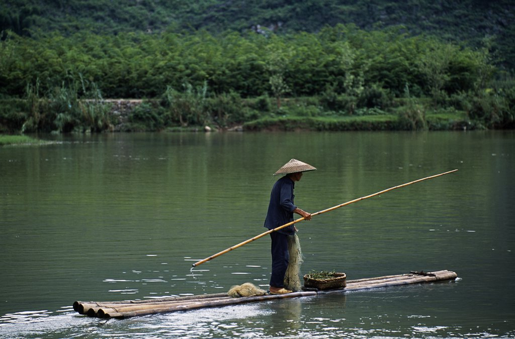 Yulong River, Nr Yangshuo, Guangxi Province A fisherman poles his bamboo raft on the placid river set amidst some of South China's finest karst scenery. : Stock Photo