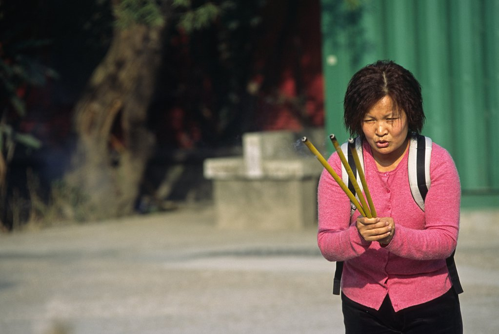 Stock Photo: 4272-3883 A woman offers incense at the foot of the Tian Tan Buddha on Lantau Island, Hong Kong.