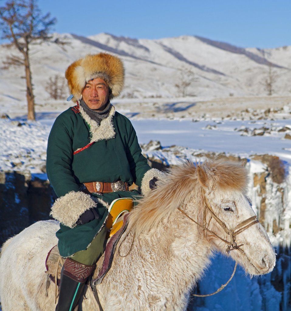 Stock Photo: 4272-39013 Mongolia, Ovorkhangai, Orkkhon Valley. A man sits on horseback by a frozen waterfall on the Orkhon River.
