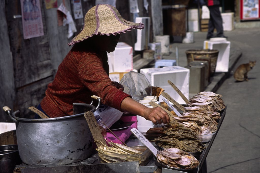 A woman lays out dried seafood to sell to visitors arriving at the Tanka village of Tai O on Lantau Island Hong Kong. : Stock Photo