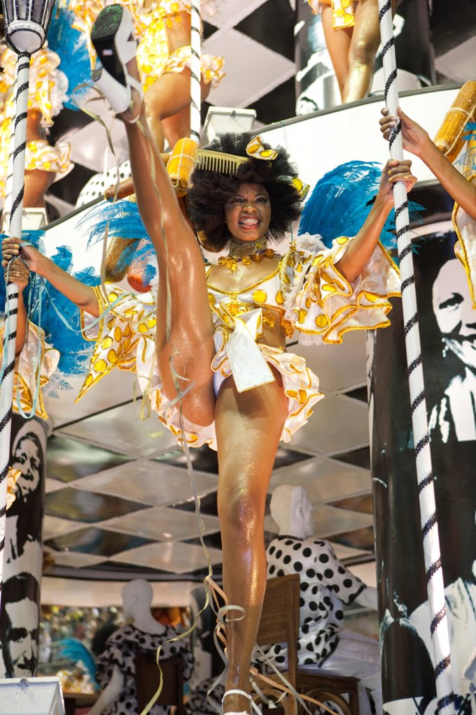 Stock Photo: 4272-39864 South America, Rio de Janeiro, Rio de Janeiro city, a highkicking costumed dancer with a comb in her hair at carnival in the Sambadrome Marques de Sapucai
