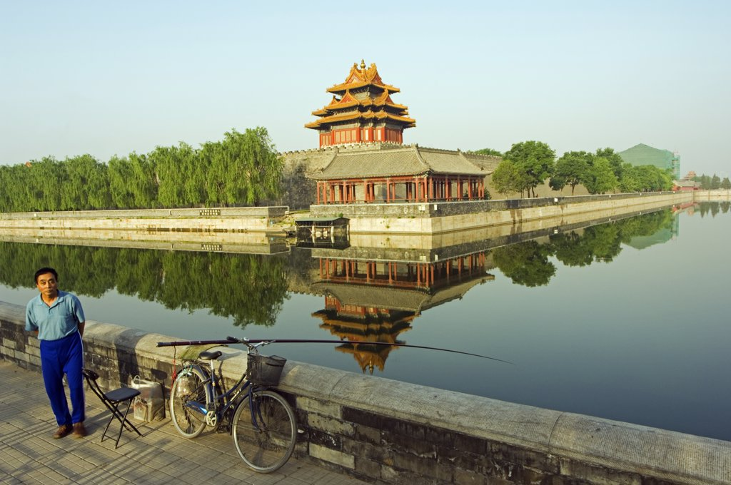 Stock Photo: 4272-4050 A man fishing in the moat with a reflection of the Palace Wall Tower of The Forbidden City Palace Museum, Zijin Cheng, Beijing, China