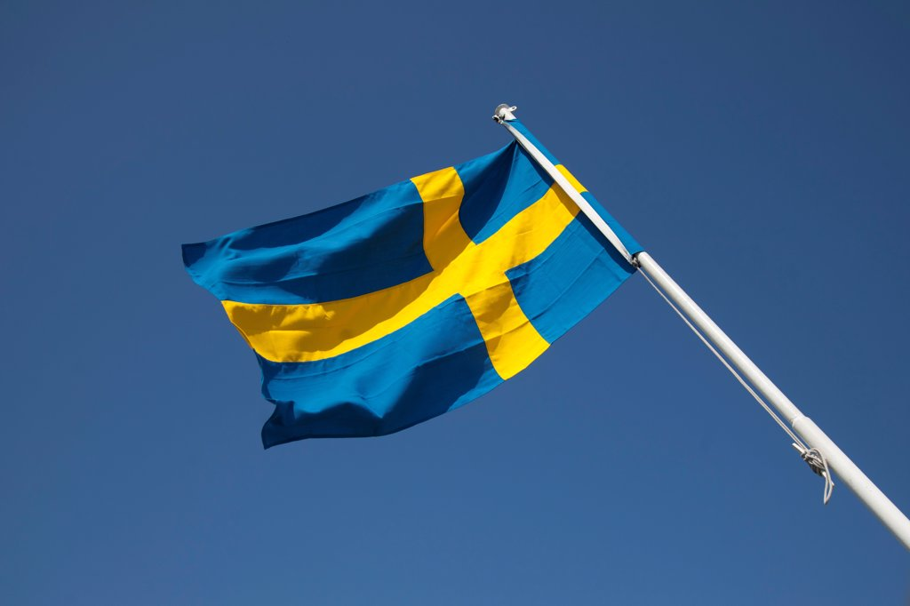 Gothenburg, Sweden. The Swedish national flag flies from the back of a city ferry. : Stock Photo