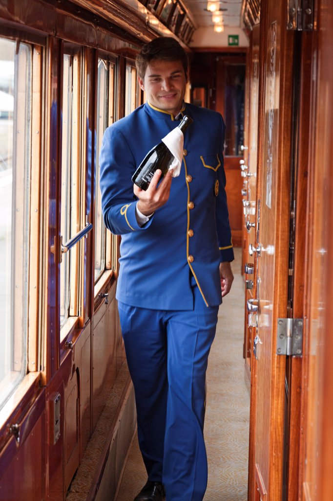 Stock Photo: 4272-42147 A steward on the Venice Simplon Orient Express train, bringing champagne to guests on board, Italy