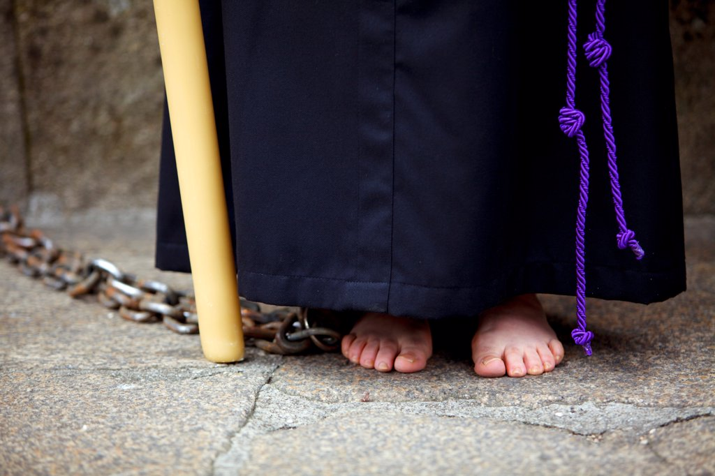 Stock Photo: 4272-42703 Santiago de Compostela, Galicia, Northern Spain, Detail of a Nazareners robe with a rope serving as a belt, chains, feet and a candlestick during Semana Santa
