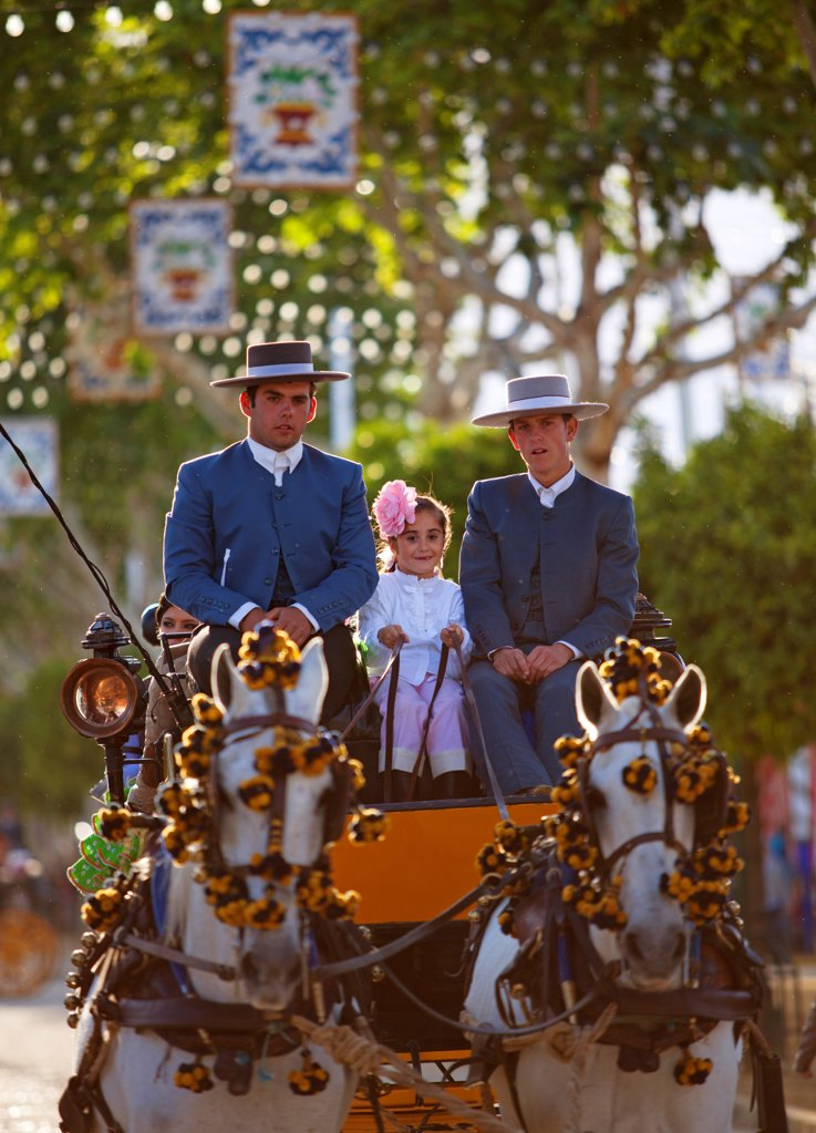 Stock Photo: 4272-42773 Seville, Andalusia, Spain, Two men and a girl in traditional clothes on a carriage drawn by horses at the Feria de Abril